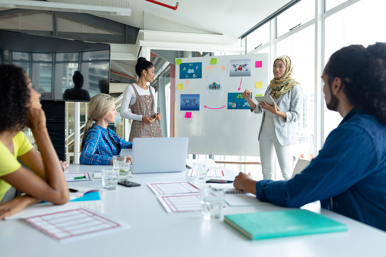 Front view of Mixed-race businesswoman in hijab giving presentation on flip chart during meeting in a modern office